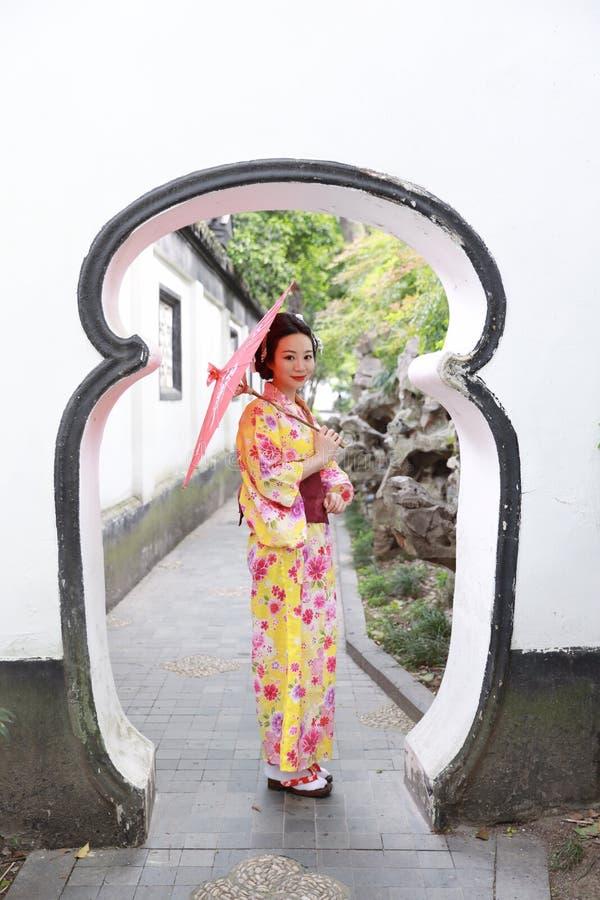A mulher bonita japonesa asiática tradicional veste o quimono em um suporte do parque do jardim da mola pelo bambu aprecia o guar fotos de stock