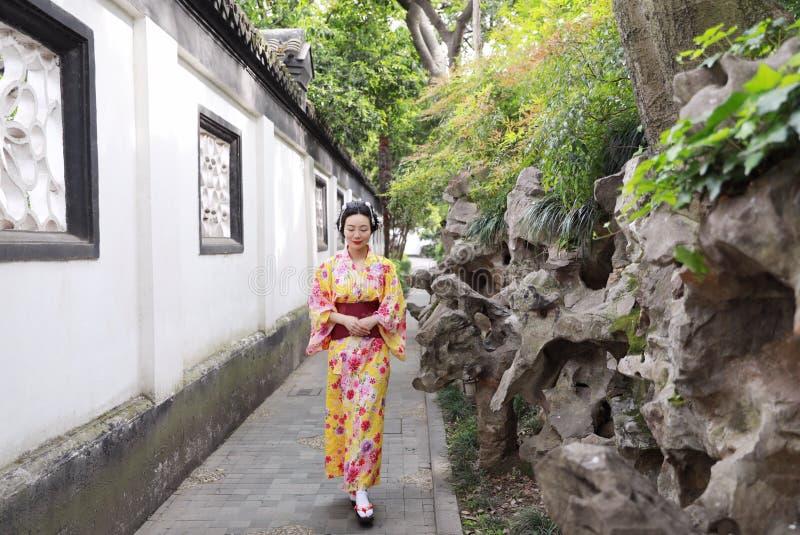 A mulher bonita japonesa asiática tradicional veste o quimono em um suporte do parque do jardim da mola pelo bambu aprecia o temp fotos de stock royalty free