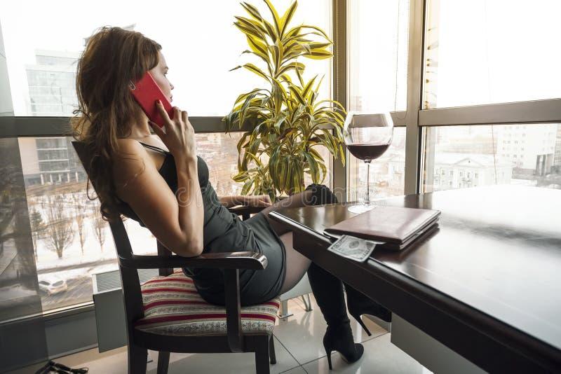 Mulher bonita jovem sentada em uma mesa em um café bebendo lentamente uma taça de vinho olhando pela janela panorâmica com uma fotografia de stock royalty free