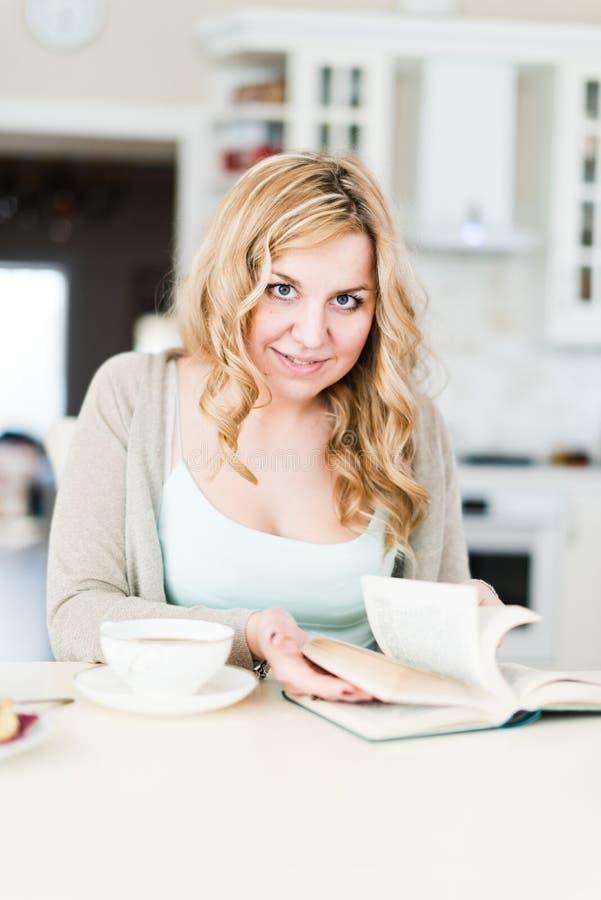 A mulher bonita lê um livro interessante foto de stock royalty free