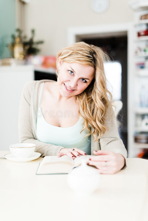 A mulher bonita lê um livro interessante foto de stock
