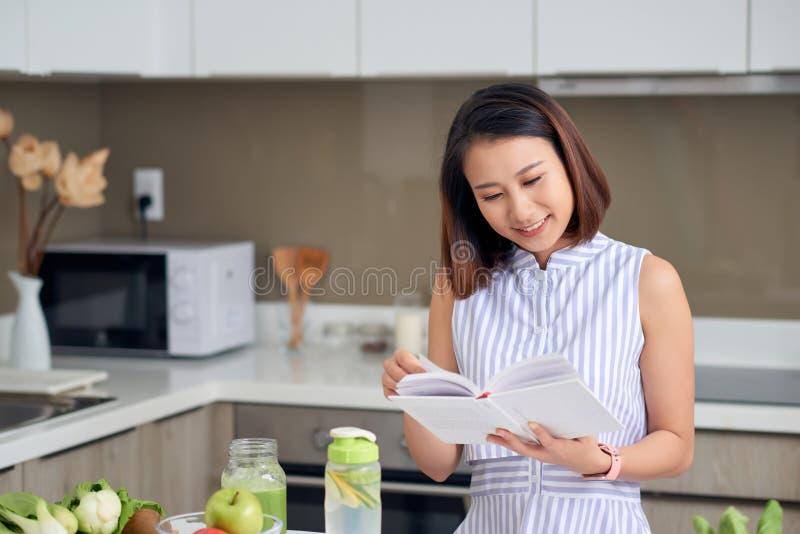 Mulher bonita lendo receita para fazer bebida de detox na cozinha fotos de stock