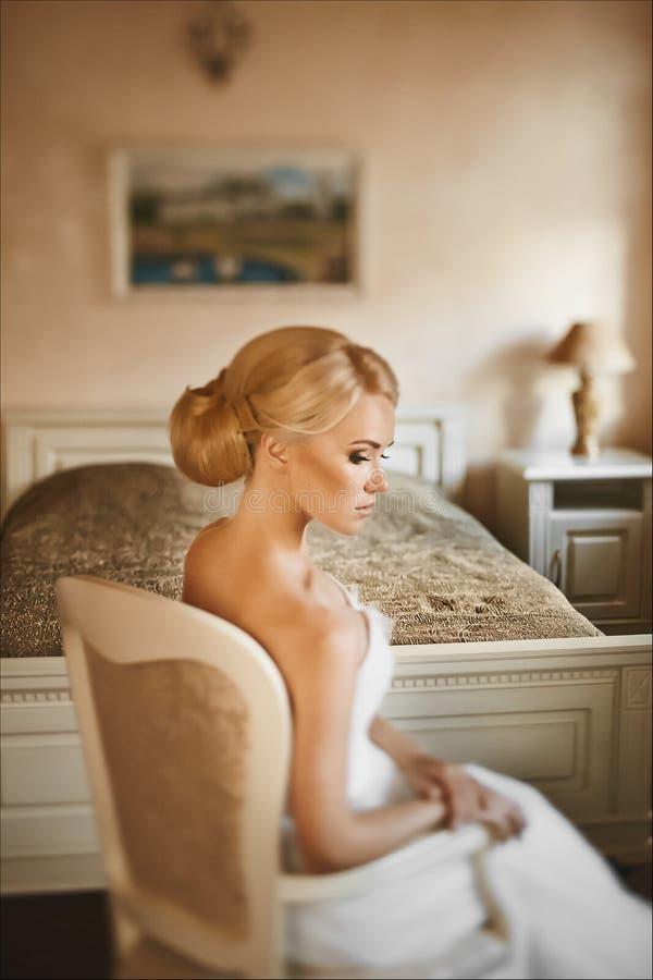 A mulher bonita loura nova com um corpo perfeito e com penteado à moda do casamento em um vestido branco senta-se em uma poltrona imagem de stock royalty free