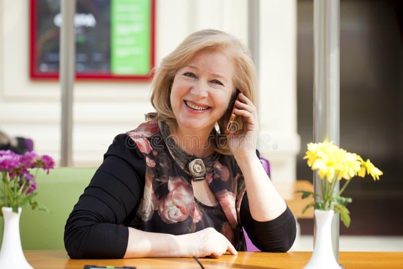A mulher bonita madura está chamando um telefone celular ao sentar-se imagem de stock royalty free