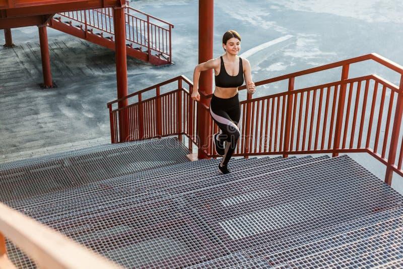 Mulher bonita magro atlética nova que corre acima as escadas que fazem o cardio- treinamento do intervalo no sportwear elegante p fotos de stock royalty free