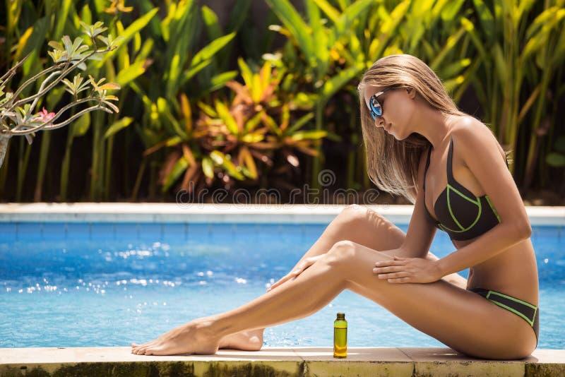 Mulher bonita magro nova no biquini que aplica o óleo imagem de stock royalty free