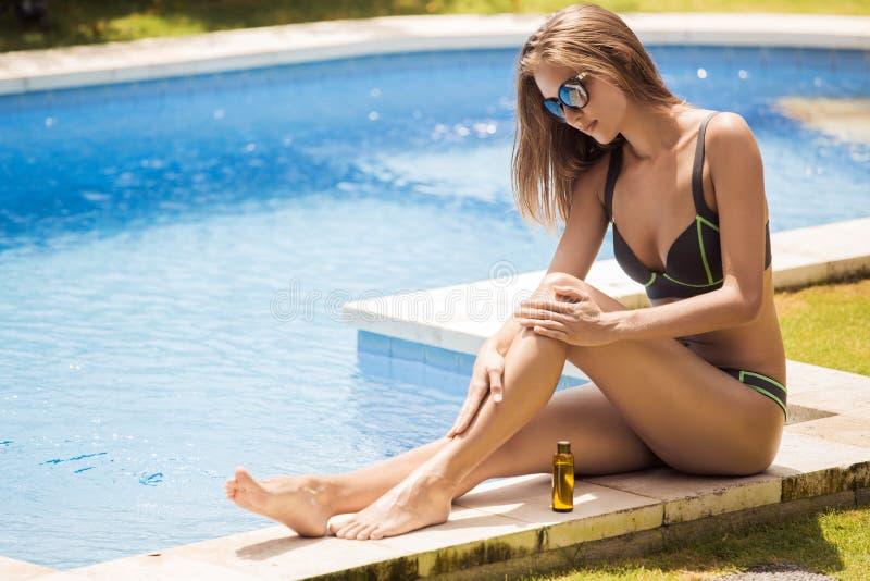 Mulher bonita magro nova no biquini que aplica o óleo fotos de stock royalty free