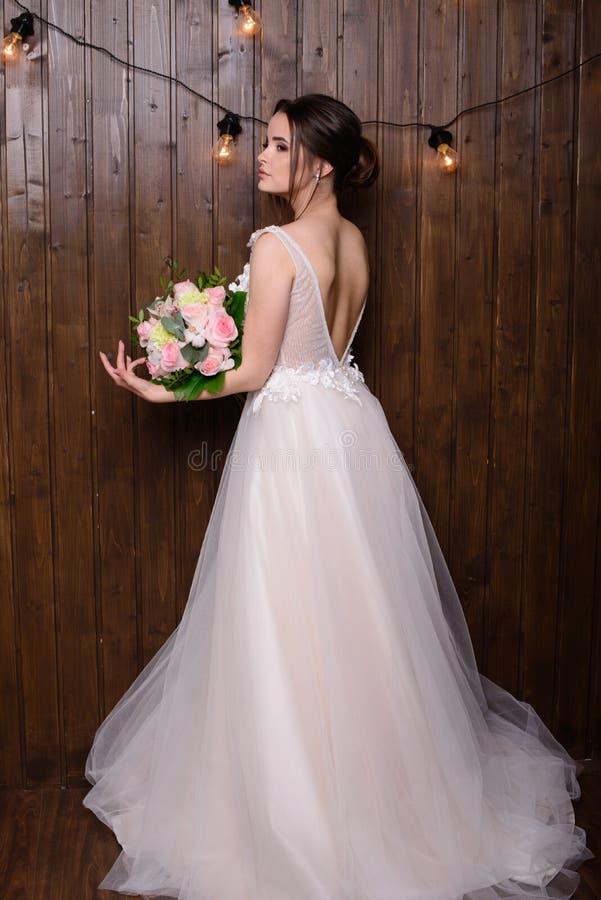 Mulher bonita magro que veste o vestido de casamento luxuoso no fundo de madeira Noiva lindo que guarda flores imagens de stock