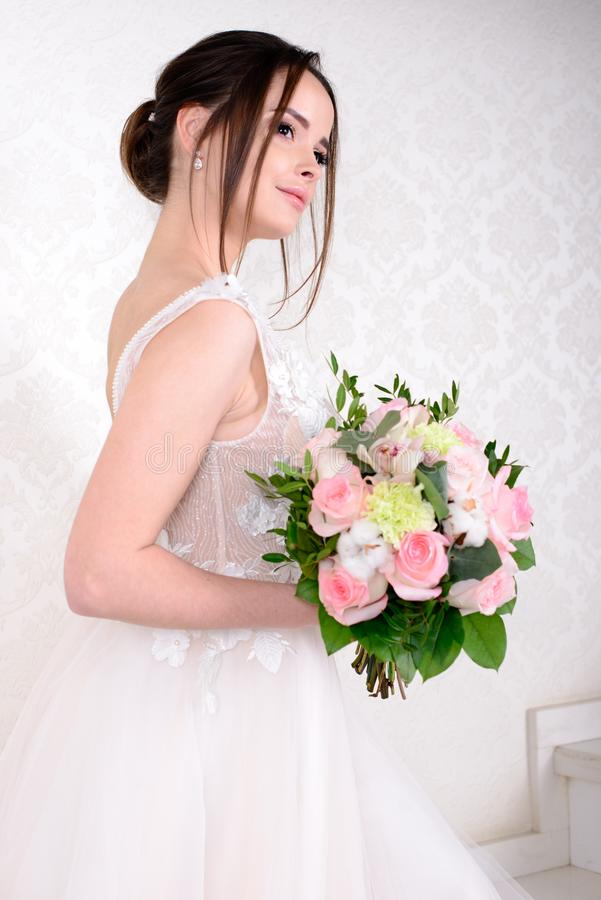 Mulher bonita magro que veste o vestido de casamento luxuoso sobre o fundo branco do estúdio Noiva lindo que guarda flores fotos de stock