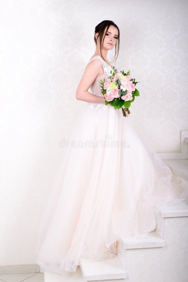 Mulher bonita magro que veste o vestido de casamento luxuoso sobre o fundo branco do est?dio Noiva lindo que guarda flores foto de stock royalty free