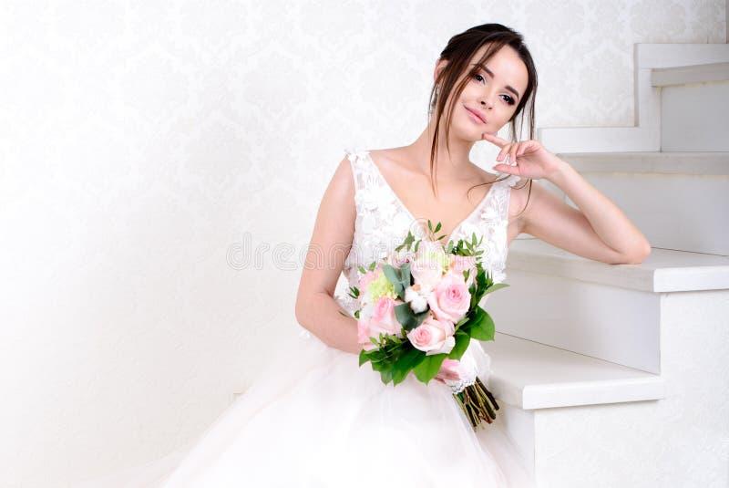 Mulher bonita magro que veste o vestido de casamento luxuoso sobre o fundo branco do est?dio Noiva lindo que guarda flores fotografia de stock