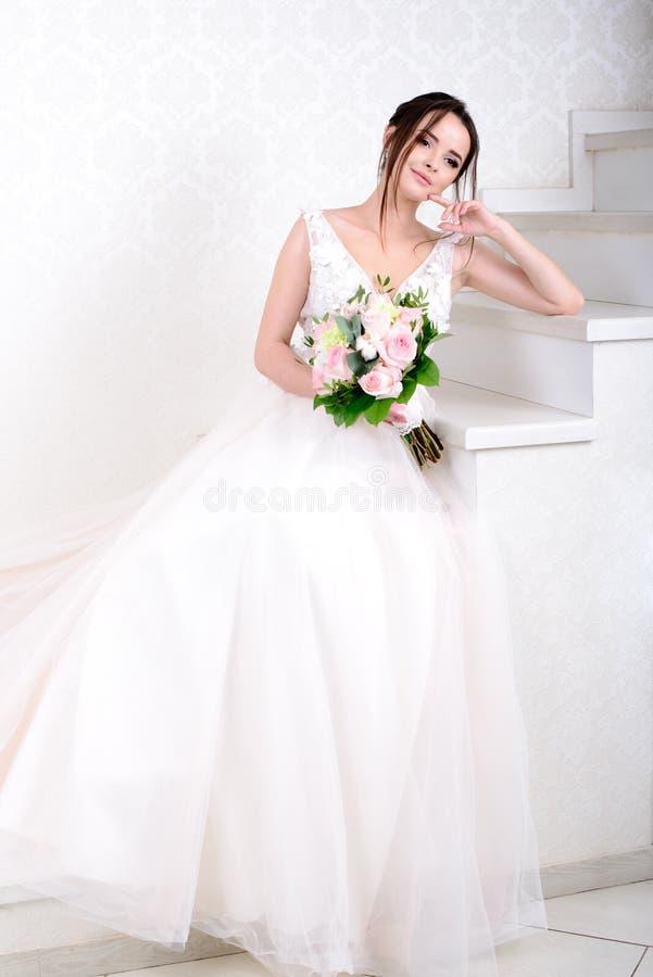Mulher bonita magro que veste o vestido de casamento luxuoso sobre o fundo branco do est?dio Noiva lindo que guarda flores fotos de stock royalty free