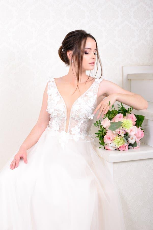 Mulher bonita magro que veste o vestido de casamento luxuoso sobre o fundo branco do est?dio Noiva lindo que guarda flores imagem de stock royalty free