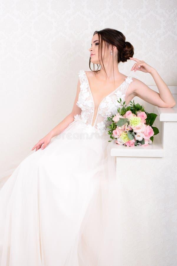 Mulher bonita magro que veste o vestido de casamento luxuoso sobre o fundo branco do est?dio Noiva lindo que guarda flores fotos de stock