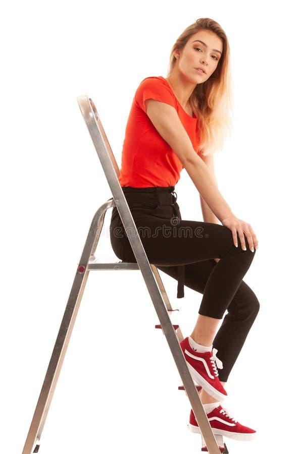 Mulher bonita, menina que veste o retrato vermelho da camisa de t da fêmea 'sexy' com a cara da beleza que levanta perto da escad foto de stock