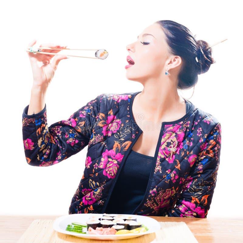 Mulher bonita moreno sedutor que come o sushi com hashis & grande prazer isolado no retrato branco do fundo imagens de stock royalty free