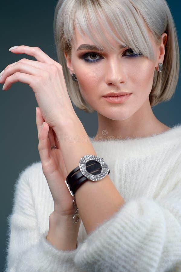 A mulher bonita mostra o bracelete na mão no fundo azul fotografia de stock