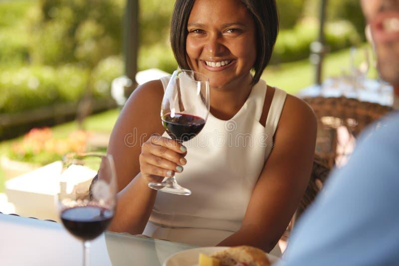 Mulher bonita na adega com um vidro do vinho tinto imagem de stock