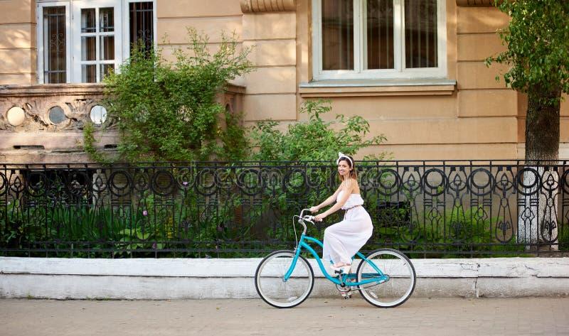 A mulher bonita na bicicleta do vintage está montando ao longo da rua da cidade imagens de stock