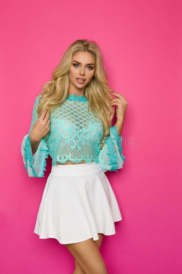 Mulher bonita na blusa do laço de turquesa e em Mini Skirt On Pink Background branco imagens de stock royalty free