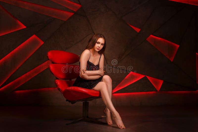 Mulher bonita na cadeira vermelha que levanta no estúdio imagens de stock royalty free