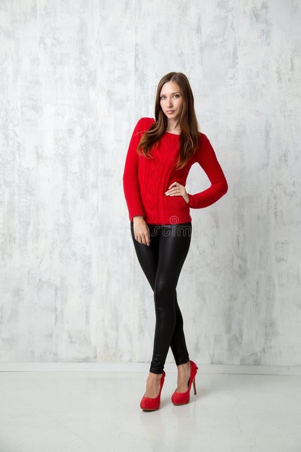 Mulher bonita na camiseta vermelha no levantamento dos saltos altos foto de stock
