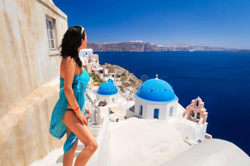 Mulher bonita na cidade de Oia da ilha de Santorini, Grécia imagens de stock