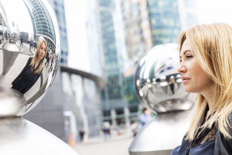 Mulher bonita na cidade grande do centro Refletido no espelho Close-up imagem de stock