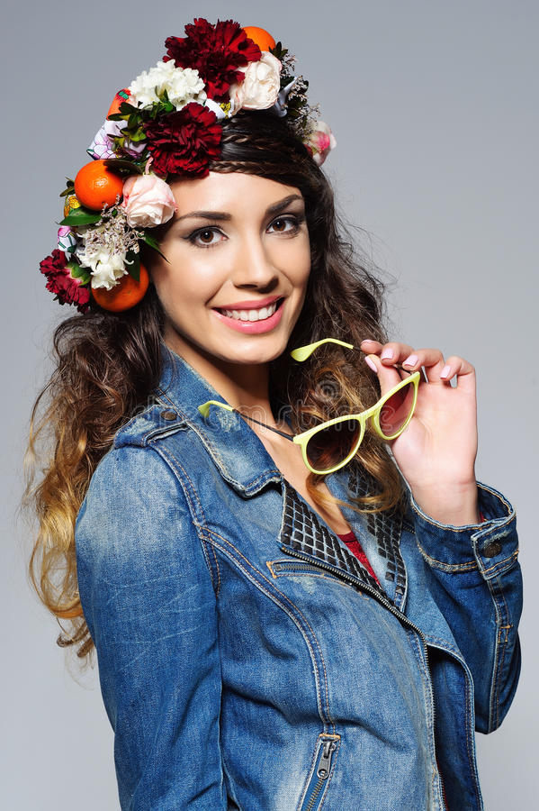 Mulher bonita na coroa da flor que guarda óculos de sol foto de stock royalty free
