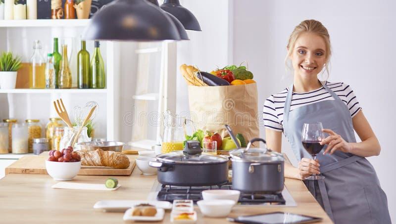 A mulher bonita na cozinha est? bebendo o vinho tinto imagem de stock royalty free