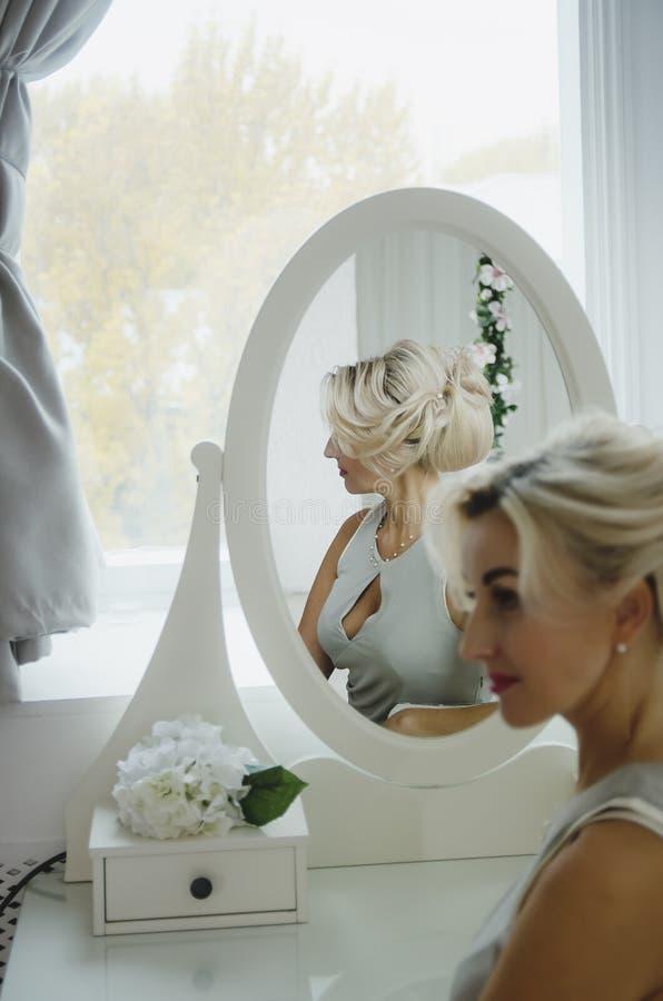 Mulher bonita na frente de um espelho, interior chique imagem de stock