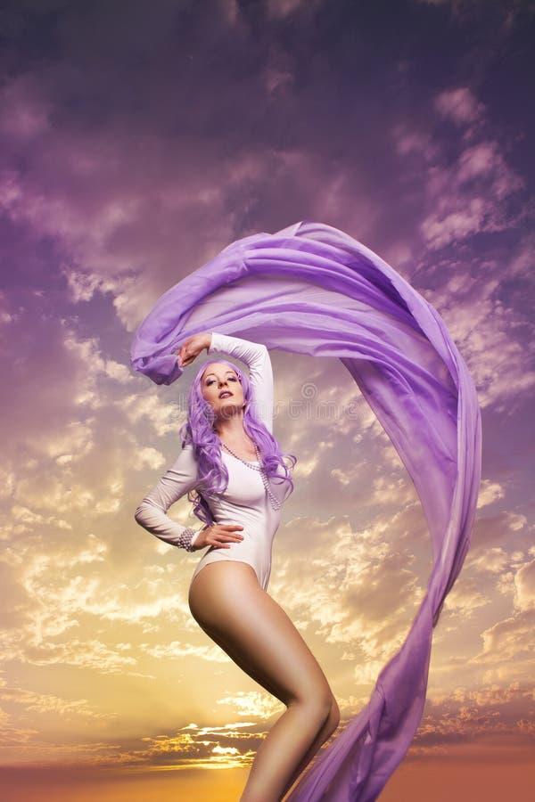 Mulher bonita na frente do fundo da nuvem fotografia de stock