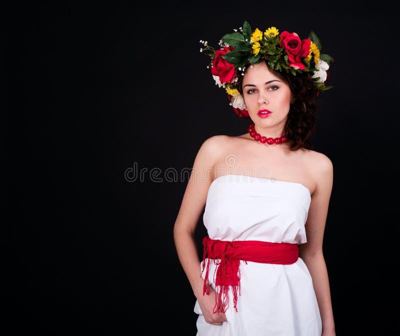 Mulher bonita na grinalda da flor, no vestido branco e na faixa vermelha imagens de stock