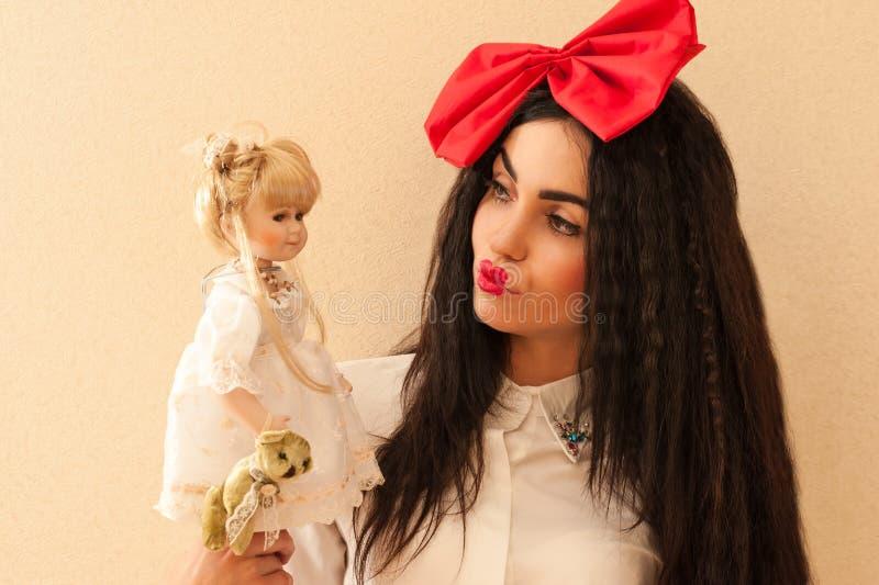 Mulher bonita na imagem de uma boneca que guarda uma boneca imagens de stock royalty free