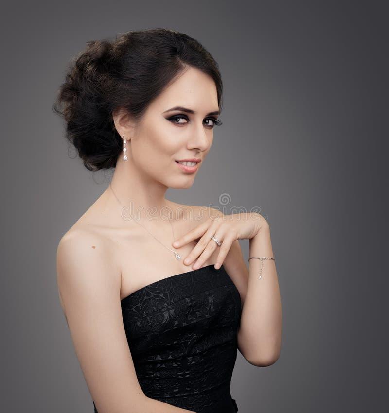 Mulher bonita na joia vestindo preta do vestido de noite foto de stock royalty free