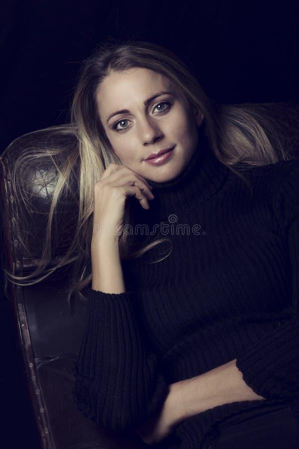 Mulher bonita na luminosidade reduzida que senta-se em uma conversão artística do sofá de couro fotos de stock