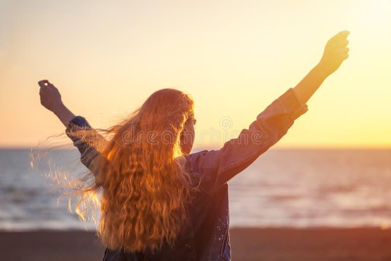 Mulher bonita na praia que aprecia a liberdade do ar fresco no sunse foto de stock