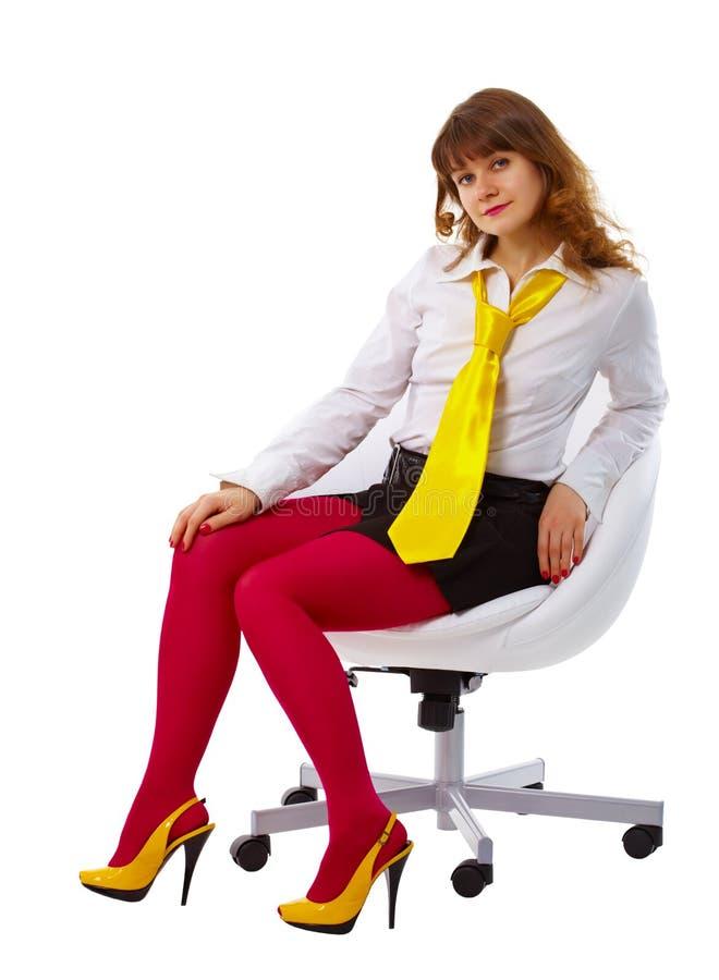 Mulher bonita na roupa brilhante em uma cadeira imagens de stock