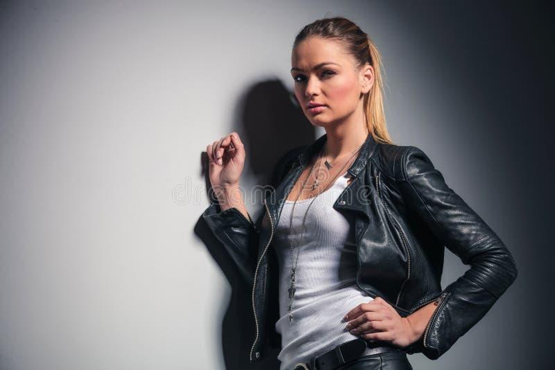 Mulher bonita na roupa de couro que inclina-se na parede cinzenta imagens de stock