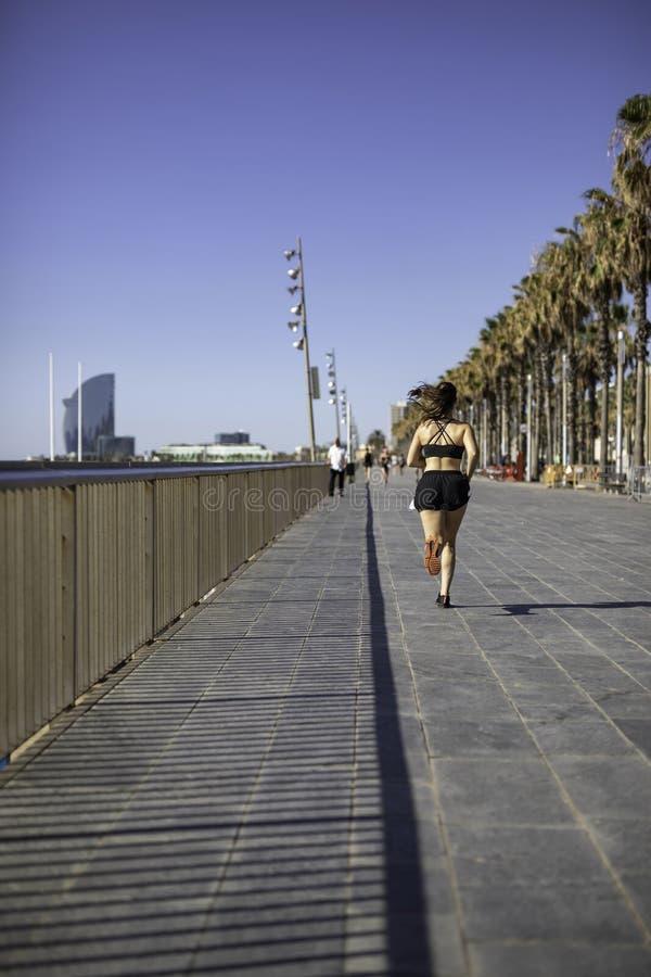 Mulher bonita na roupa do esporte que corre na frente marítima em Barcelona & em x28; ESPANHA fotografia de stock royalty free