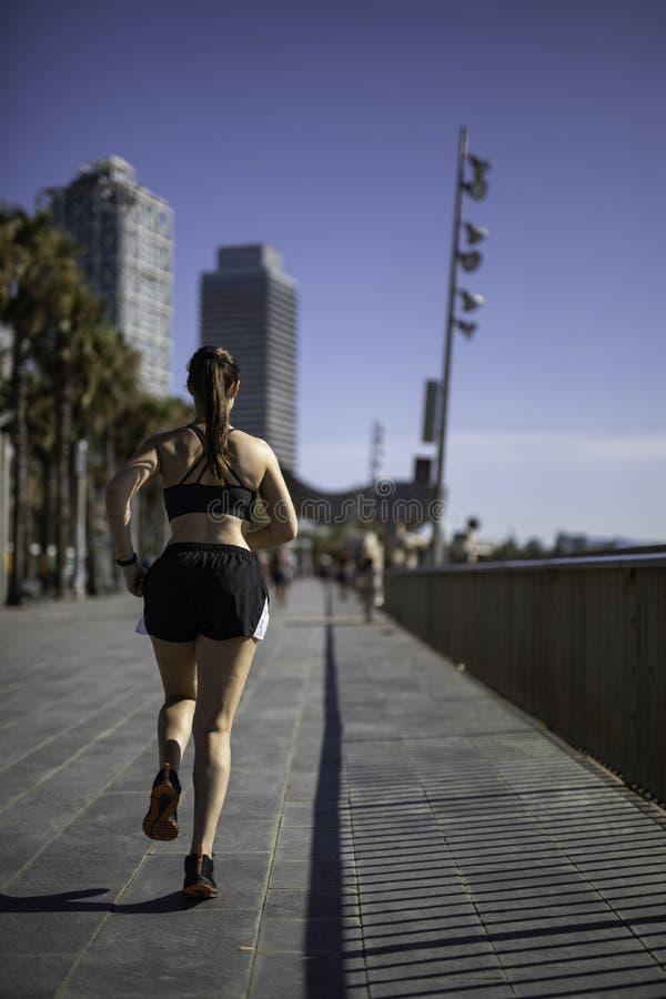 Mulher bonita na roupa do esporte que corre na frente marítima em Barcelona & em x28; ESPANHA foto de stock royalty free