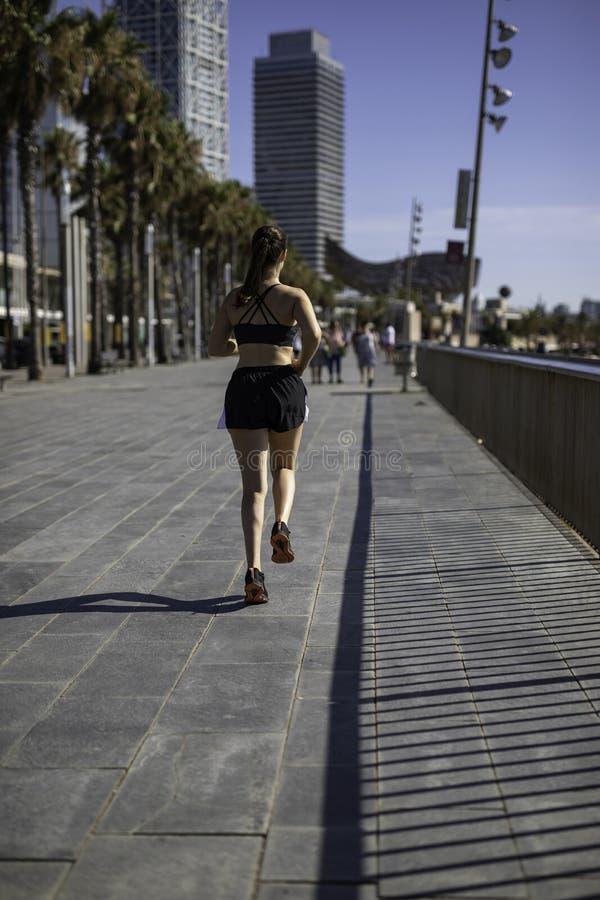 Mulher bonita na roupa do esporte que corre na frente marítima em Barcelona & em x28; ESPANHA imagem de stock royalty free