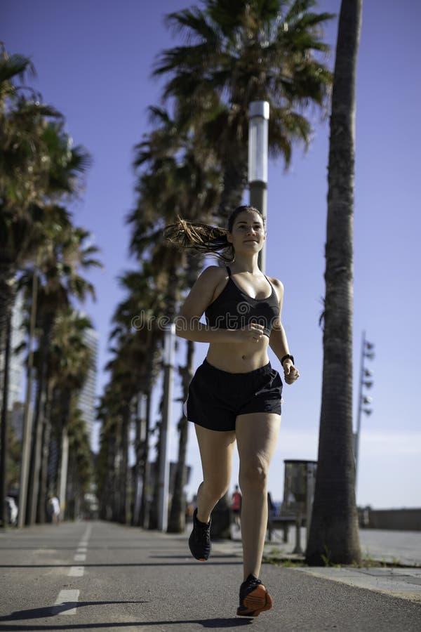 Mulher bonita na roupa do esporte que corre na pista da bicicleta na frente marítima em Barcelona & em x28; ESPANHA fotografia de stock