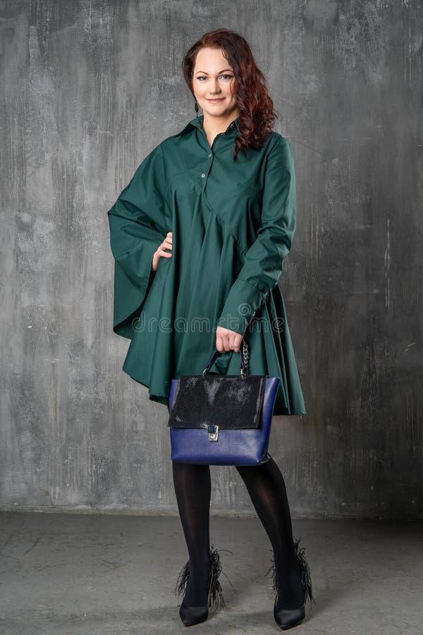 Mulher bonita na roupa elegante que levanta para a câmera no estúdio imagem de stock