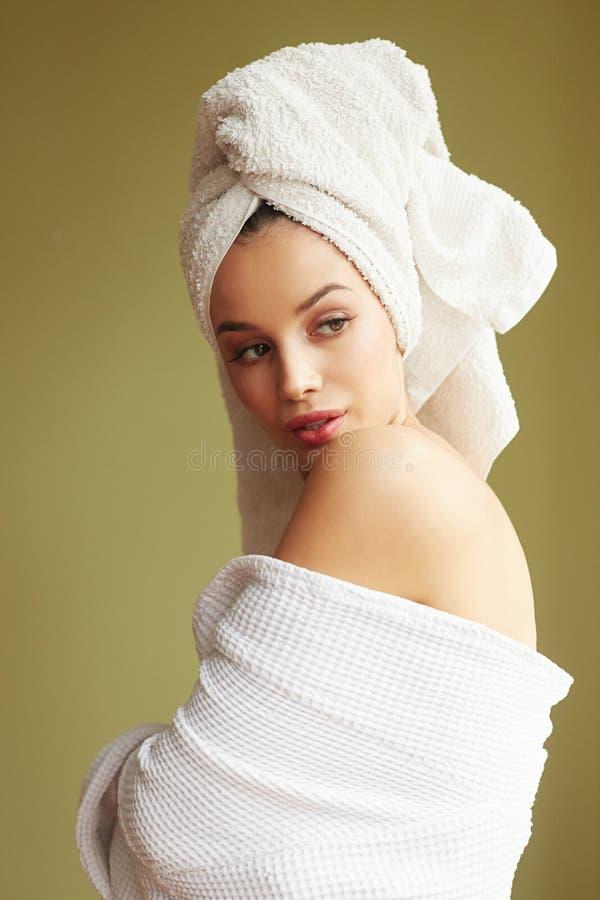 Mulher bonita na veste de banho com uma toalha em sua cabeça que olha pensativamente fora da câmera imagens de stock royalty free