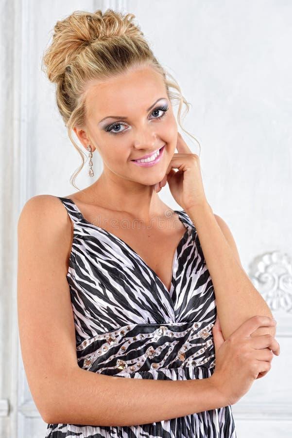 A mulher bonita na zebra modelou o vestido longo no interior branco. fotografia de stock royalty free