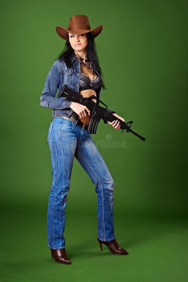 Mulher bonita nas calças de brim com o rifle no verde imagem de stock royalty free