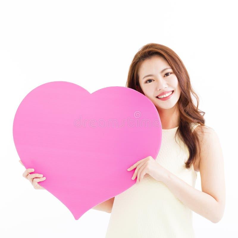 Mulher bonita no amor e em guardar a forma do coração imagem de stock