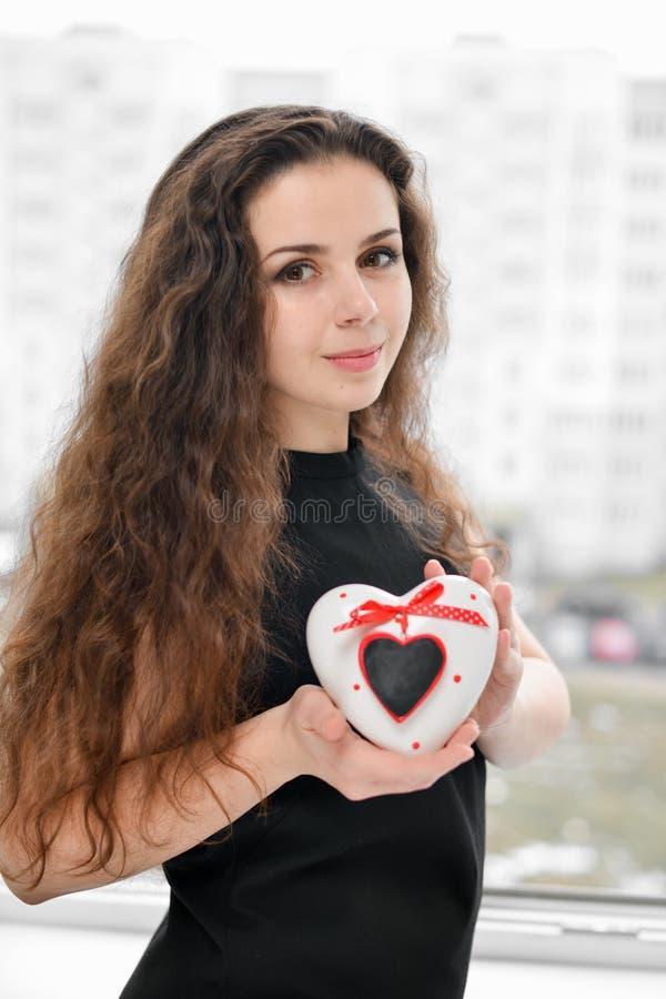 Mulher bonita no amor que prende caixa heart-shaped imagens de stock royalty free