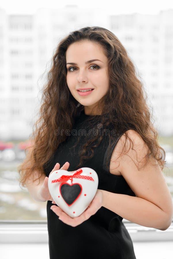 Mulher bonita no amor que prende caixa heart-shaped imagem de stock